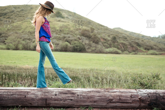 Boho style young woman walking along log