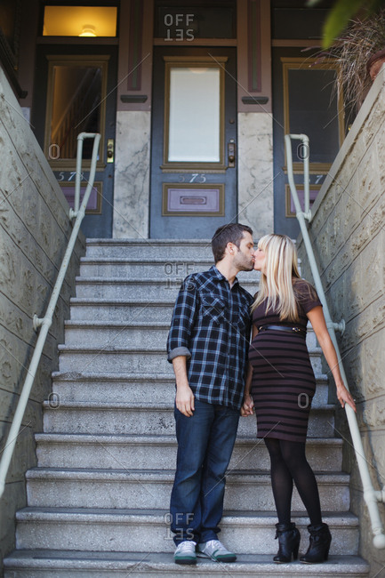 Pregnant mid adult woman kissing boyfriend outside house stairway