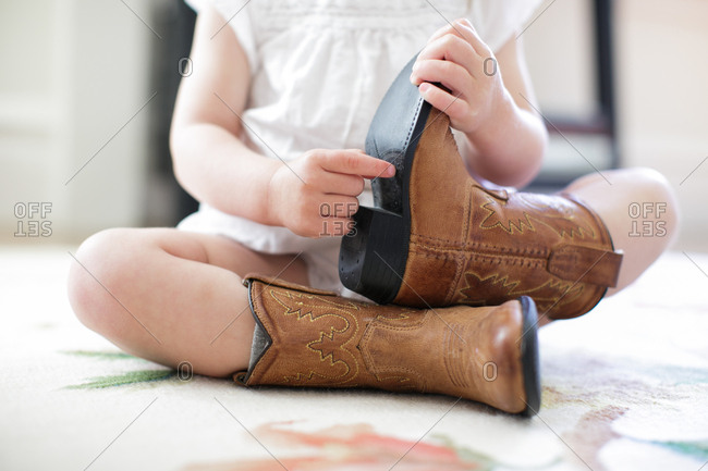 Neck down view of female toddler sitting on floor wearing cowboy boots