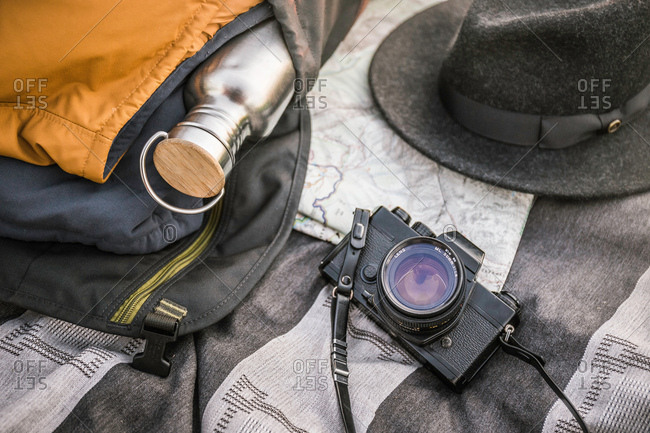 Still life of blanker, SLR camera, drinking flask and hat
