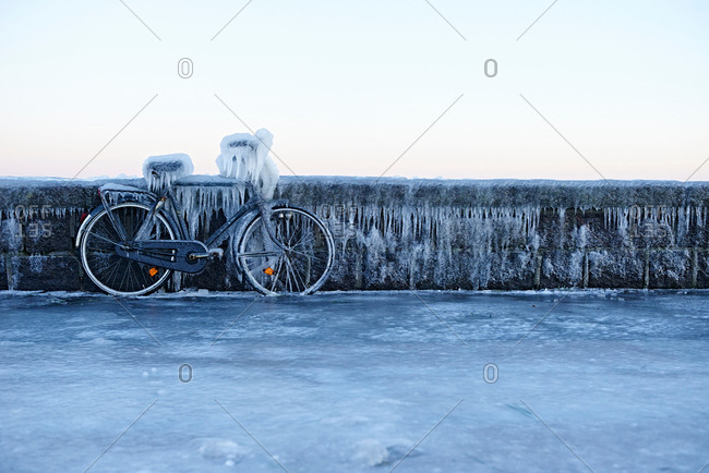 Bicycle leaning against wall, covered in ice