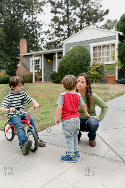 Woman talking to sons at bottom of driveway at home