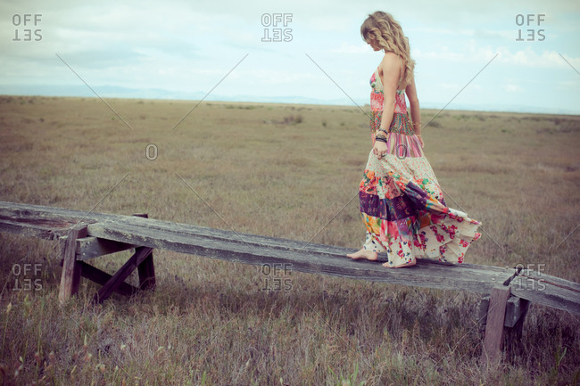 Young woman in boho maxi dress walking on elevated wooden walkway in landscape