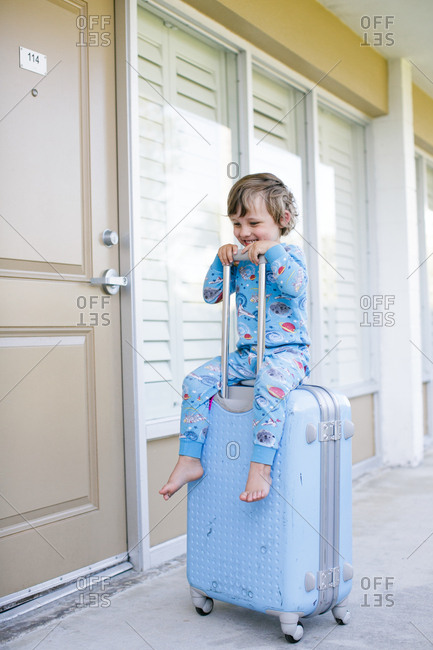 Boy in pajamas sitting on wheeled suitcase outside chalet