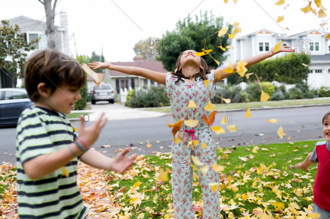 Siblings playing with autumn leaves in garden