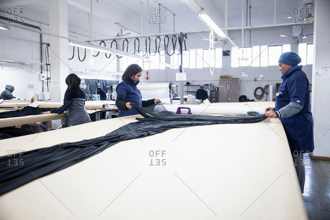Factory workers unrolling textiles on work table in clothing factory