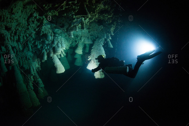 "Scuba diver exploring unique natural formations known as ""bells"" in submerged caves beneath the jungle"