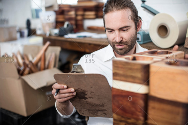 Man with clipboard checking wooden products in factory