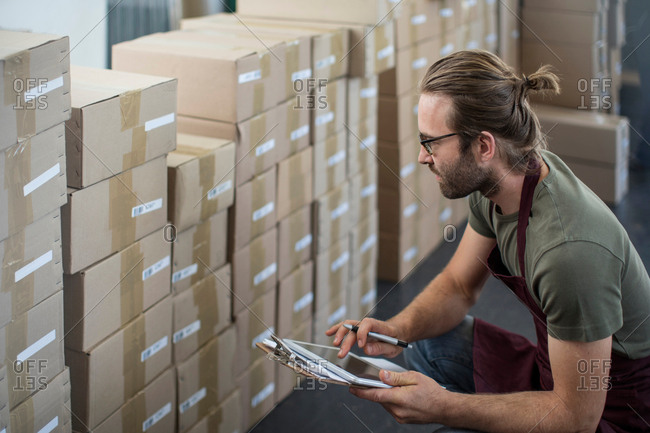 Man using digital tablet to check boxed products in factory storeroom