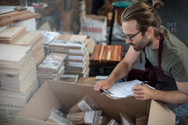 Man with clipboard checking boxed products in factory