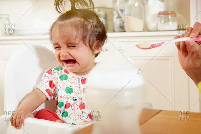 Baby girl crying while being fed breakfast by mother