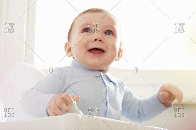 Blue eyed baby boy on high chair