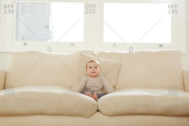 Portrait of baby boy sitting on sofa