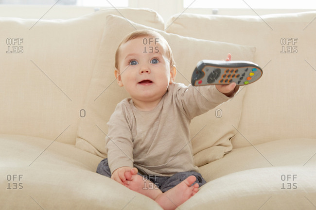 Baby boy sitting on sofa holding remote control