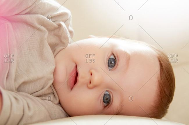 Close up portrait of blue eyed baby boy lying on sofa