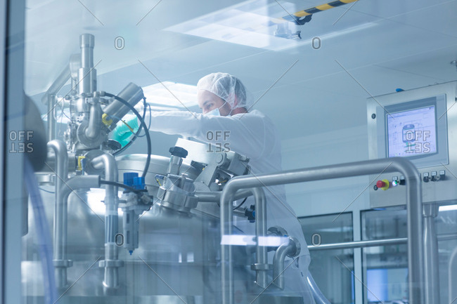 Worker operating pharmaceutical production equipment in pharmaceutical plant