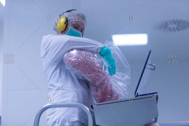 Worker pouring tablets into sorting machine  in pharmaceutical plant