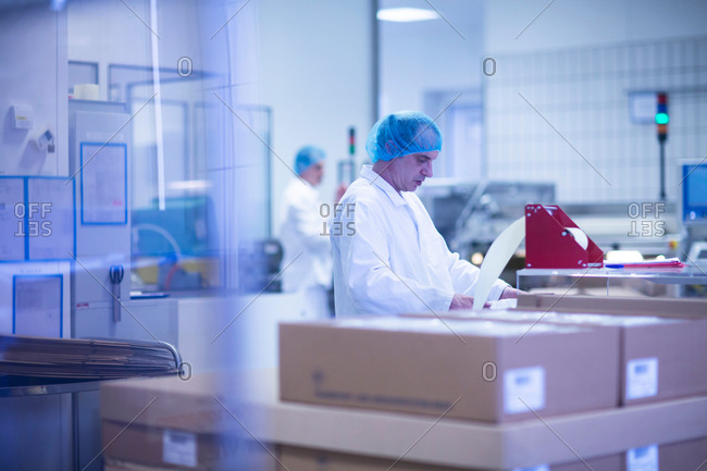 Workers packaging pharmaceutical products on production line in pharmaceutical plant