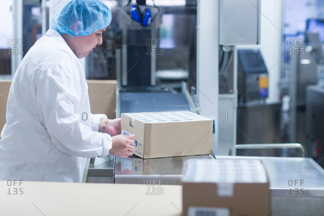Worker packaging pharmaceutical products in pharmaceutical plant