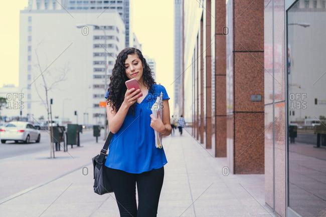 Young woman walking along street, using smartphone
