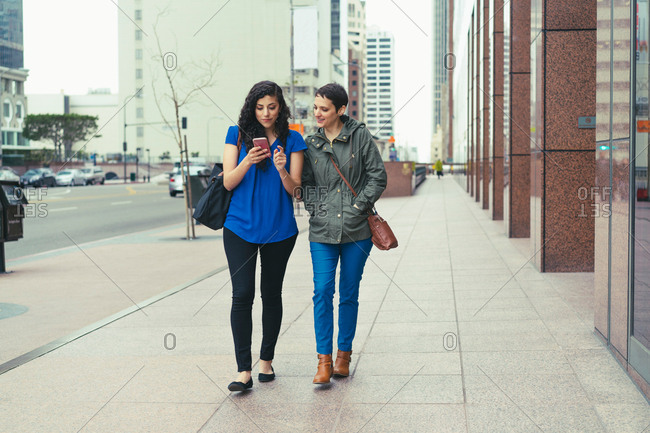 Two female friends walking along street, looking at smartphone