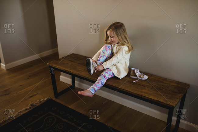 Girl sitting on bench putting on trainer shoe