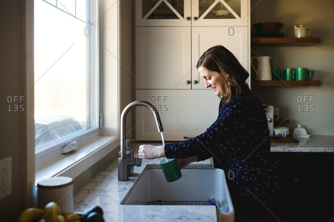 Woman filling up cup at kitchen sink