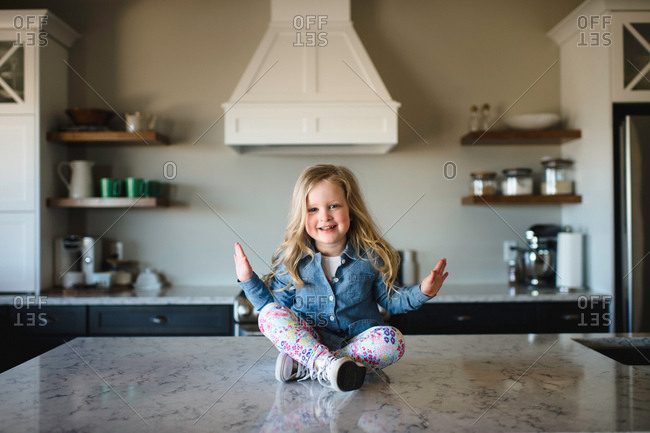 Portrait of girl sitting cross legged on kitchen counter
