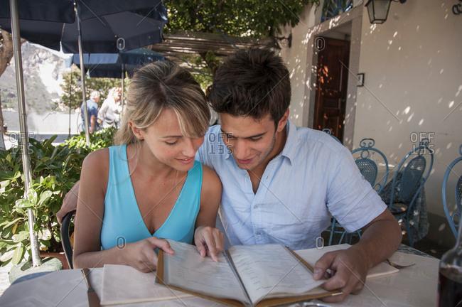 Couple looking at menu at outdoor restaurant, Lake Maggiore, Italy