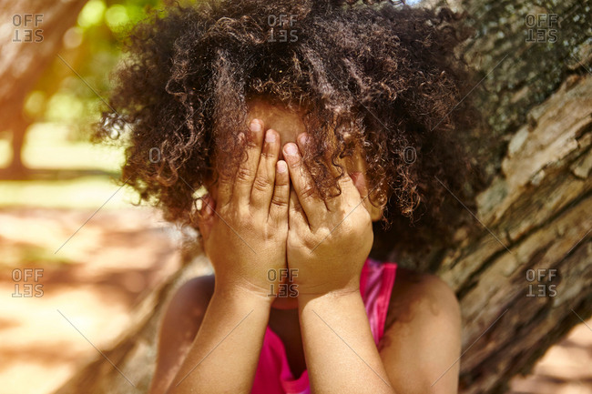 Young girl standing outdoors, covering face with hands