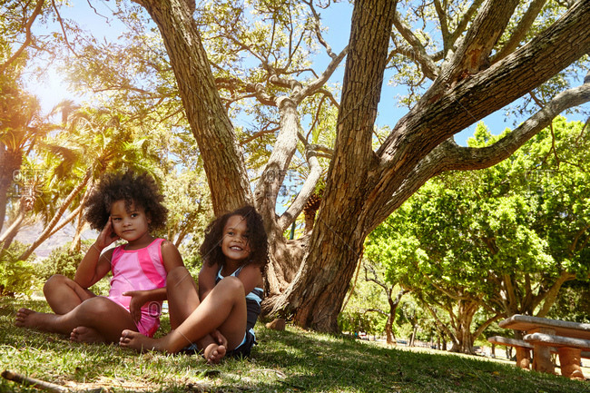 Portrait of two young sisters, sitting beside tree