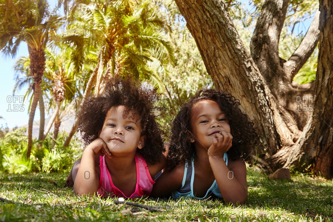 Portrait of two young sisters, lying on grass beside tree