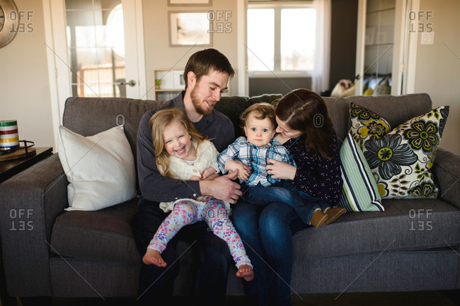 Portrait of mid adult parents with girl and baby boy on sofa