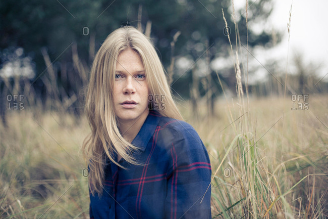 Portrait of young woman with long blond hair in field of long grass