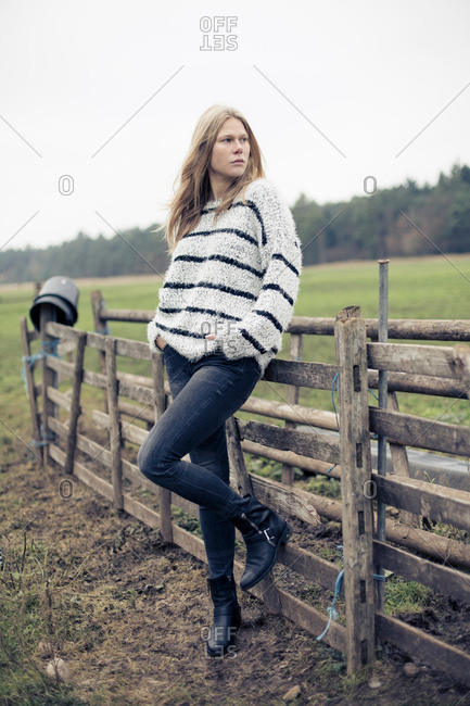 Stylish young woman leaning against wooden fence in field