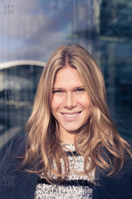 Portrait of young woman with long blond hair outside office building