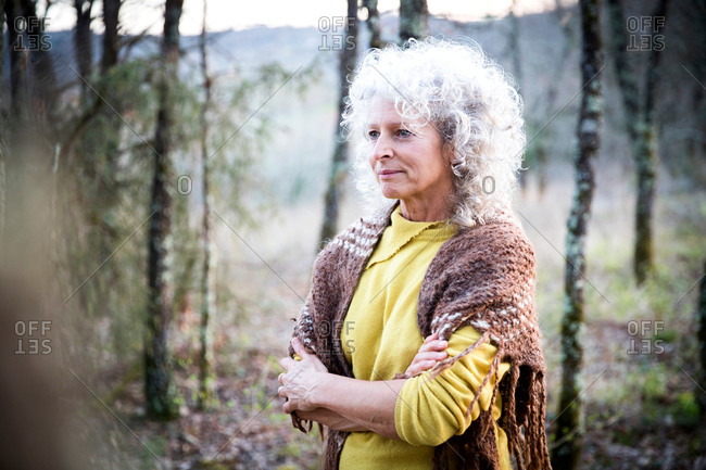 Mature woman standing in woodland with arms folded