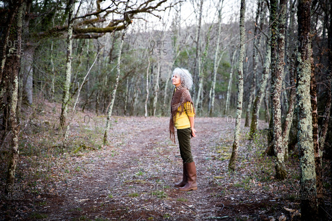 Mature woman standing in woodland looking