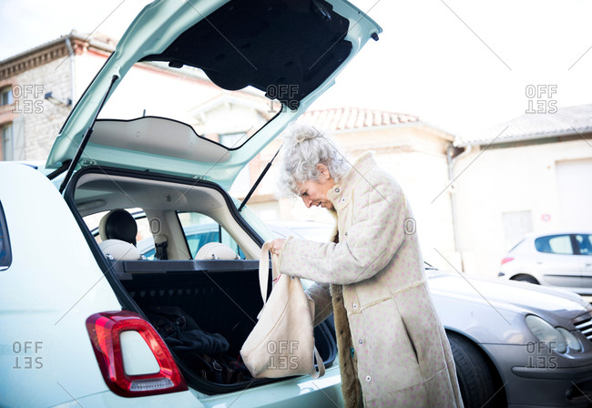 Mature woman with shopping bag looking in car trunk