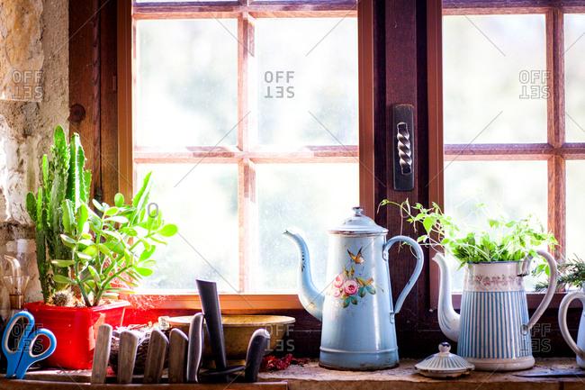 Rustic coffee pots and pot plants on kitchen windowsill