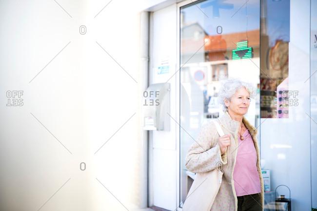 Mature woman shopper walking past local bank