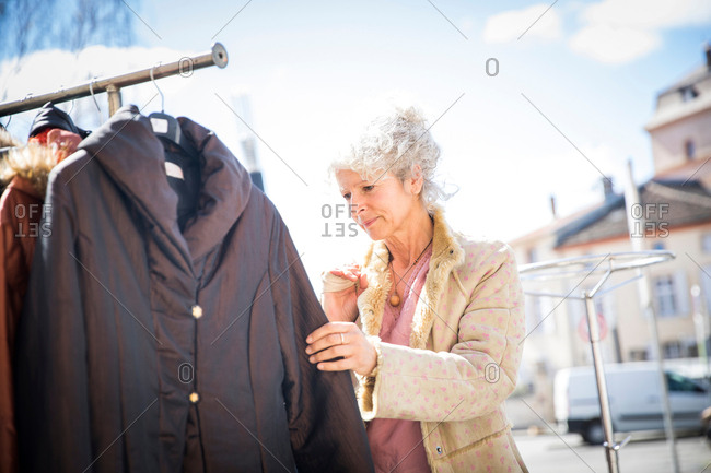 Mature woman shopper looking at clothes at local market