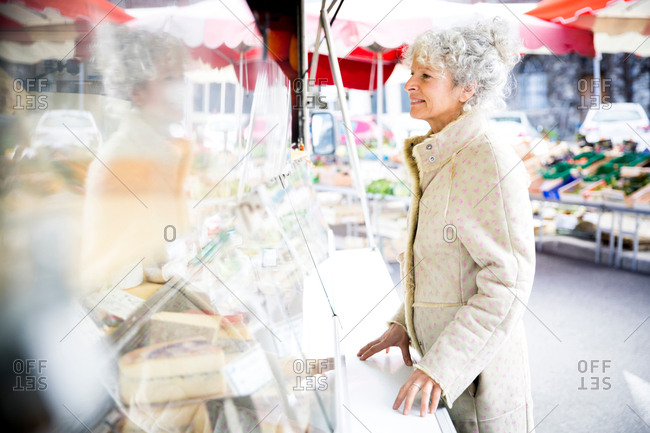 Mature female shopper buying cheese at local French market