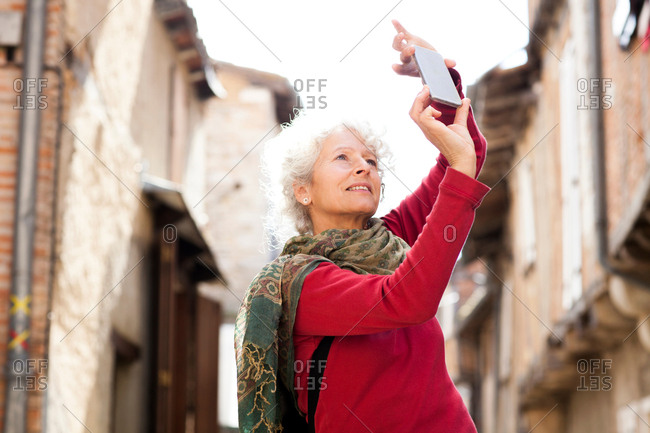 Woman taking photograph in street, Bruniquel, France