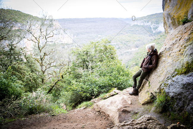 Woman leaning against rock looking away at view, Bruniquel, France