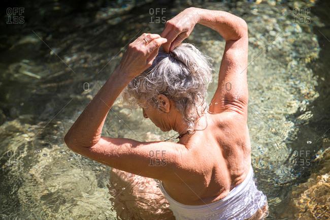 Woman in water wearing swimsuit tying hair