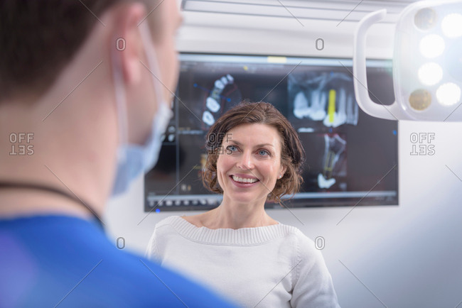 Dentist showing x-rays on screen to patient in dental surgery