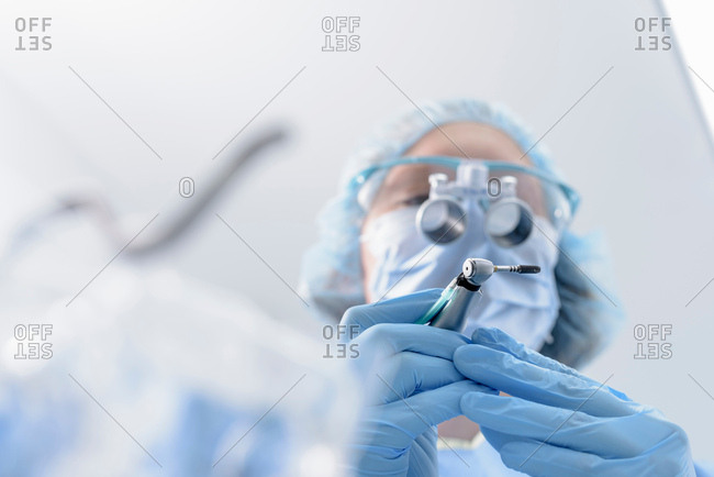 Dentist preparing dental implant in dental surgery