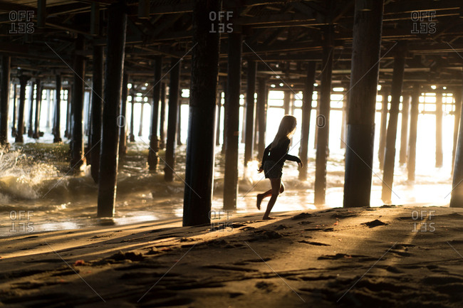 Silhouette of girl running from lapping waves underneath Santa Monica pier, California, USA