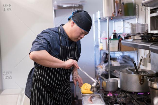 Chef in kitchen preparing food